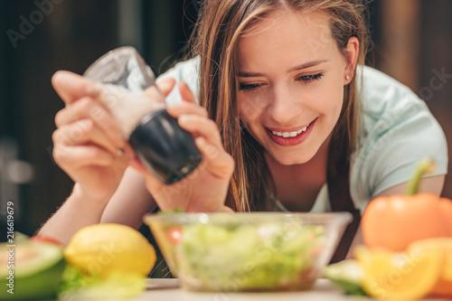 Attractive girl preparing salad