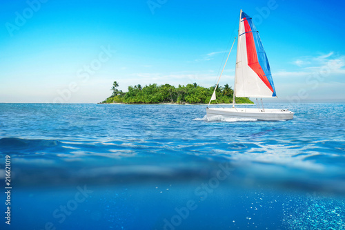 sea surface summer wave background with sailboat. Exotic water landscape with clouds on horizon. Natural tropical water. Travel tropical island. Ocean Underwater nature