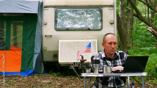 4K. American man traveler works on laptop near trailer. Freelance life