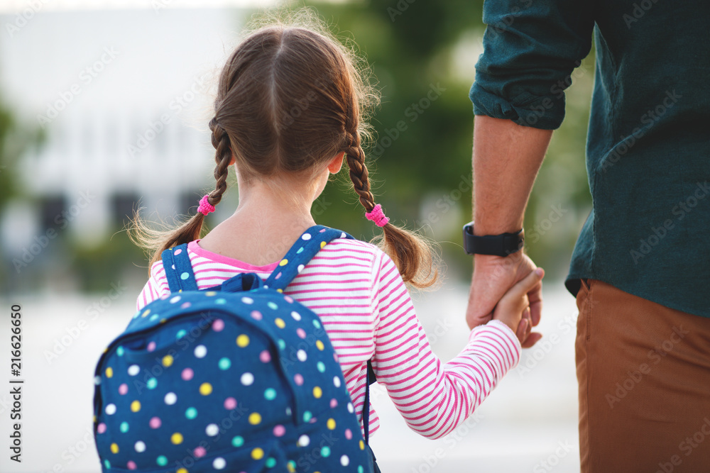 Fototapeta first day at school. father leads  little child school girl in first grade