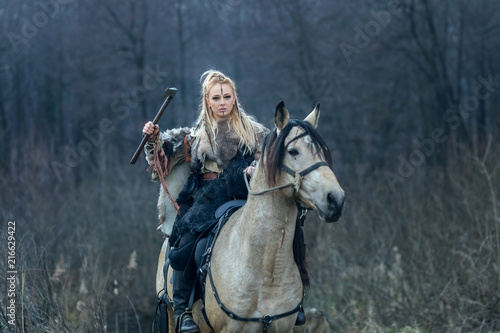 Fotografie, Obraz  Blonde warrior viking woman riding horse with ax in hand against forest background ready to attack