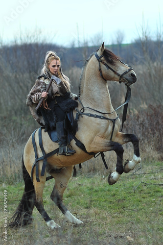 Photo  Blonde young Viking warrior woman riding a horse with ax in hand