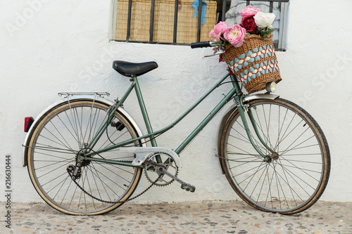 Poster Fiets Vintage bicycle parked with basket of beautiful flowers. Old bike on the street leaning on the perimeter with window