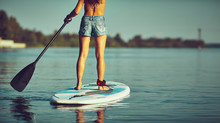 SUP Stand Up Surf Girl With Paddle At Sunset