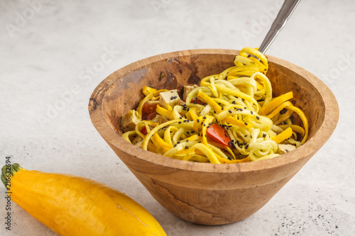 Raw vegan zucchini noodles with tofu and tomatoes in a wooden bowl.