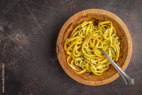 Raw vegan zucchini noodles in a wooden bowl, top view, dark background