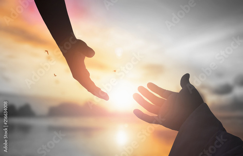 Fotografie, Obraz  The concept of God's salvation:silhouette of helping hand concept and internatio