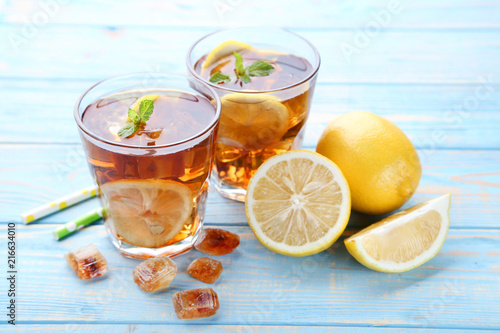 Foto  Ice tea in glasses with lemon and mint leafs on wooden table