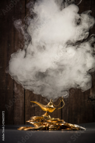 Magic lamp of wishes on stacks of gold coins with smoke