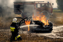 Firefighter Extinguishing A Burning Car That Caught Fire During An Accident