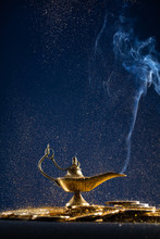 Magic Lamp Of Wishes On Stacks Of Gold Coins With Smoke Coming Out From The Lamp. Studio Shooting.