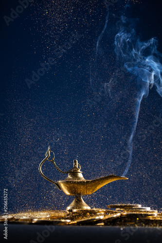 Fotografia  Magic lamp of wishes on stacks of gold coins with smoke coming out from the lamp