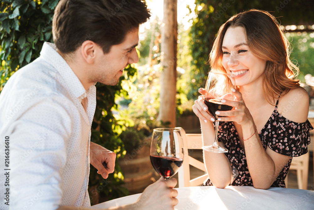 Fototapeta Loving couple sitting in cafe by dating drinking wine