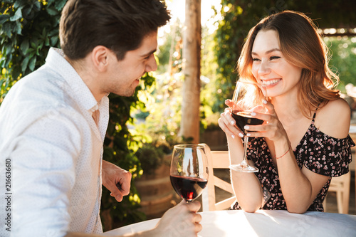 Fotografie, Obraz Loving couple sitting in cafe by dating drinking wine