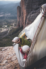 Couple Of Climbers Looking To Horizon Ready To Sleep In A Portaledge Hanging On The Wall In Los Mallos De Riglos, Spain