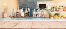 Bar With The Shelf Of Alcoholic Drinks. Empty Wooden Table Top For You Product Presentation.