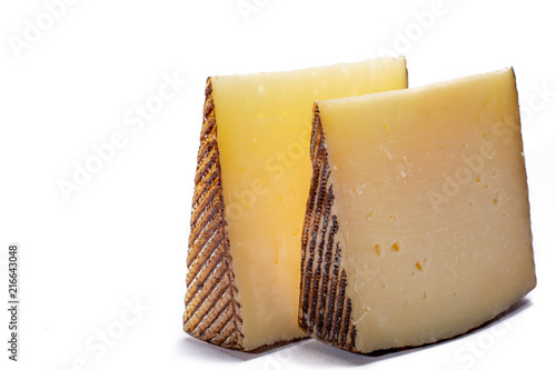 Two pieces of Manchego, queso manchego, cheese made in La Mancha region of Spain from the milk of sheep of the manchega breed, isolated on white
