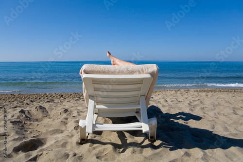 Láminas  A man is resting on a deckchair by the sea.