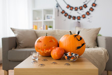 Holidays, Decoration And Party Concept - Jack-o-lantern Or Carved Pumpkin With Halloween Decorations And Treats On Wooden Table At Home Room
