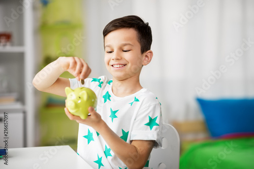 money, finances, childhood and people concept - smiling little boy putting coin into piggy bank at home