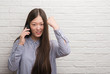Young Chinese woman over brick wall talking on the phone annoyed and frustrated shouting with anger, crazy and yelling with raised hand, anger concept