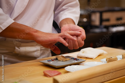 Poster Sushi bar Professional sushi chef carefully using just the right pressure to make perfect sushi with confident and dedication. Precision and Finesse at its best practice to achieve top performance in business.