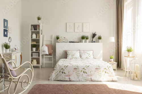 Real photo of a provencal bedroom interior with a double bed, floral sheets, shelves, plants and rocking chair