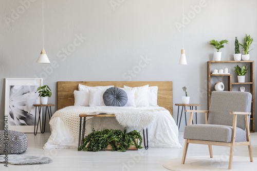 Photo  Patterned armchair and plants in bright bedroom interior with poster next to wooden bed