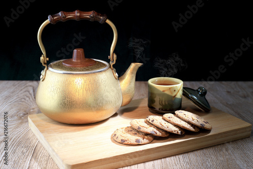 Staande foto Thee Hot tea in the teapot and ceramics cup with cookies chocolate chip on wooden board. as Black background. Foods and drink concept. Warm lights tone.