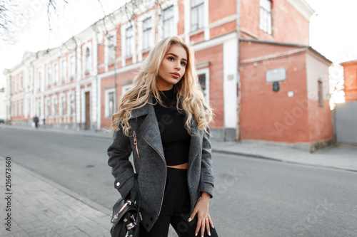 Obraz Beautiful young woman model with a bag in a stylish gray jacket walking outdoors in the city - fototapety do salonu