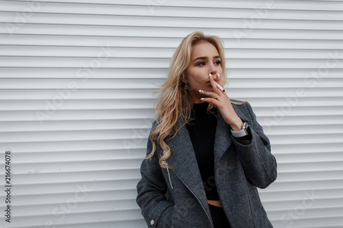Fotografia Beautiful young model woman with a cigarette in a gray fashionable jacket near a