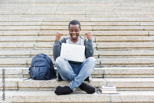 Happy successful student sitting on stairs using laptop