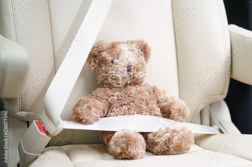 Teddy bear, fasten the seatbelt for your child safety. Child in car concept. Soft focus on the teddy bear's nose.