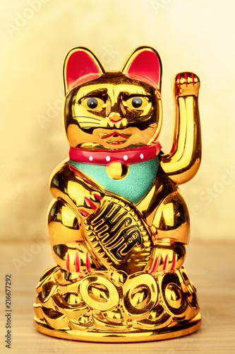 Foto op Plexiglas Asia land Maneki neko, Japanese lucky beckoning cat figurine, on a golden background with copy space
