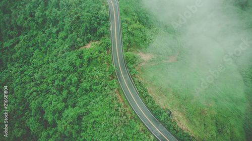 Fototapeta Aerial top view of sky road over top of mountain with fog and green jungle after raining in morning obraz na płótnie
