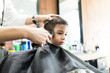 Boy Having His Hair Trimmed In Barber Shop