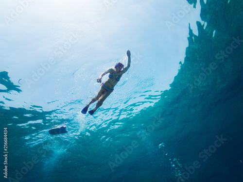 Cadres-photo bureau Plongée Girl doing swimming and snorkeling on blue deep water