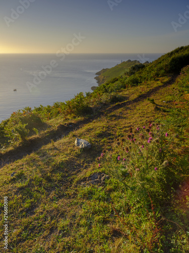 Fotobehang Grijs Summer sunrise on a clear day on the Start Point peninsula and light house on the south Devon coast, UK