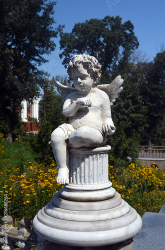 Poster Historisch mon. Little cupid angel with spread wings in the garden.