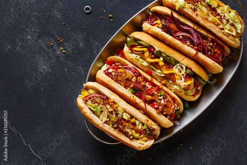 Fototapeta Hot dogs fully loaded with assorted toppings on a tray.