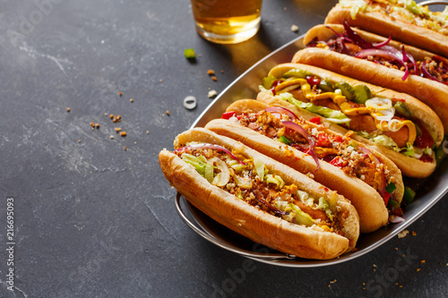 Stampa su Tela Hot dogs fully loaded with assorted toppings on a tray.