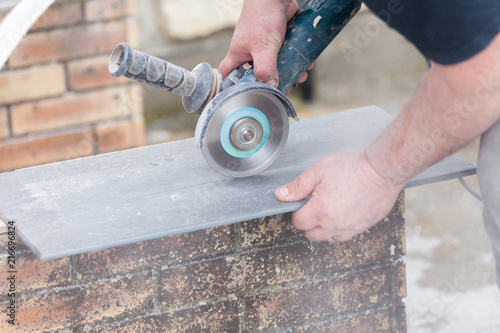 Photo  tiler cutting a tile with a grinder