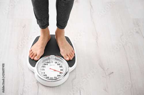 Fotografia  Woman measuring her weight using scales on floor