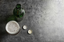 Bottle And Glass With Tasty Cold Beer On Grunge Background, Top View