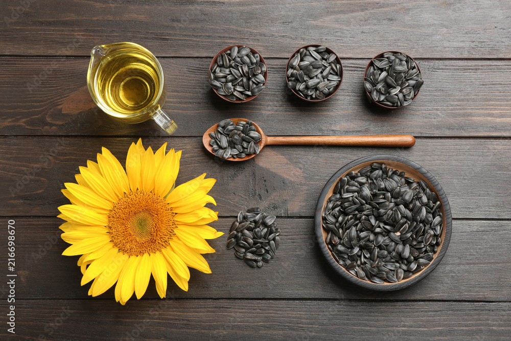 Flat lay composition with sunflower seeds and flower on wooden table