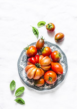 Fresh Tomatoes And Basil Leaves On A Light Background, Top View. Heirloom Tomatoes