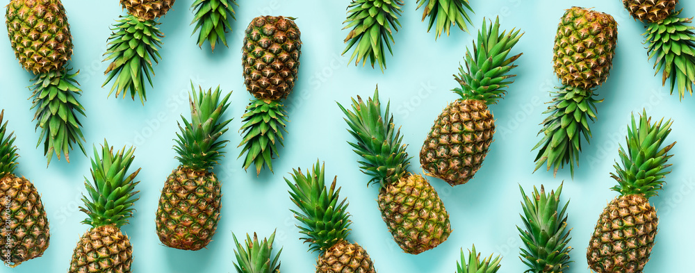 Fototapeta Bright pineapple pattern for minimal style. Top View. Pop art design, creative concept. Copy Space. Banner. Fresh pineapples on blue background.