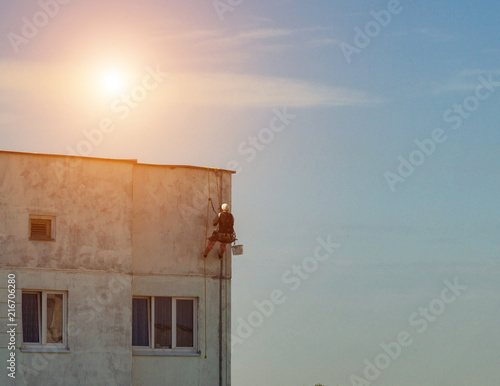 Male construction climber repairs the leaky seams in the panel house, the sun, a Wallpaper Mural