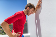 Tired Athlete Runner Man Exhausted Leaning On Wall Of Fatigue Breathing Hard After Difficult Exercise. Fitnes Person Sweating Of Sun Stroke, Migraine, Heat Exhaustion Muscle Back Pain Or Cramps.