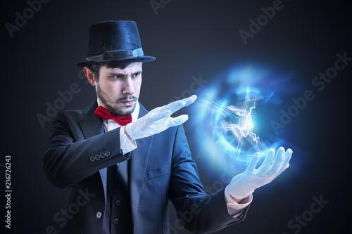 Magician or illusionist is showing bright plasma ball radiating light rays Fototapeta
